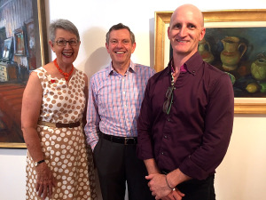 Lismore Mayor Jenny Dowell, Margaret Olley Trust representative Phillip Bacon, and Lismore Regional Gallery director Brett Adlington. Works by Olley from the gallery's collection include (left) Spare Bedroom (1970) and Lemons and Ginger Jar (c1980