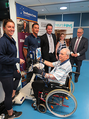 Stroke survivor Murray Shergold receiving muscle stimulation from the RT300 Functional Electrical Stimulation Ergometer at NeuroMoves in Southern Cross University's Health Clinic. Pictured l-r - Exercise Physiologists Kate Schaefer and Sam Mitchell, Graham Batten from Newcastle Permanent Charitable Foundation, and Southern Cross University's Vice-President Global, Chris Patton.