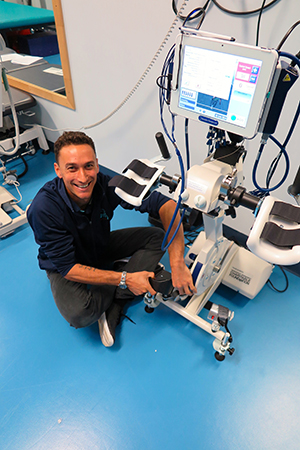 NeuroMoves exercise physiologist Sam Mitchell with the RT300 Functional Electrical Stimulation Ergometer that assists with arm and leg rehabilitation for patients with illnesses such as paraplegia, quadriplegia and stroke.
