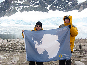 Ruth and her cousin at Neko Harbour with flag showing the continent of Antarctica.