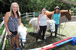 Pictured at the Horses Helping Humans property in the Gold Coast hinterland are (l-r) Narelle van Egmond, Scottish born jockey Gina Mitchell, badly injured in a race fall, and program founder Sue Spence.