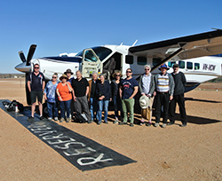 Pictured at William Creek airfield before flying over Kati Thander-Lake Eyre, now in a dramatic flood phase, are (l-r) Seair Pacific pilot and guide Kirk Campbell, Ruth Tinker, Susan Brown, Jane Griffin, John Haggerty, Andrew Binns, Jeni Binns, Emily Yorston, Mark Hartcher, Maree Beek, Jurriaan Beek, and pilot and GP Izaac Flanagan.